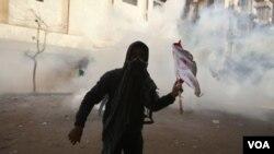 Seorang demonstran menghindari gas air mata yang ditembakkan oleh pasukan keamanan Mesir di Kairo (4/2).