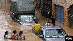 Warga bersusah payah melintasi banjir di pusat kota Hat Yai, Provinsi Songkhla, Thailand.
