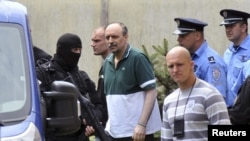 Serbian police officers escort Goran Hadzic (C, in green), after he visited his terminally ill mother in Novi Sad July 22, 2011. Serbia on Friday extradited Goran Hadzic, the last ethnic Serb wanted by the International Criminal Court in The Hague, in a s