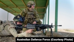 An Australian Army trainer observes an Iraqi Army soldier from the Ninewa Operations Command Commando Battalion conduct a live fire shoot with the M249 machine gun at the Taji Military Complex, Iraq.