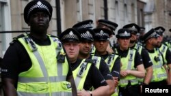 FILE - Police officers stand by during a protest against the visit of U.S. President Donald Trump, in central London, Britain, July 13, 2018.
