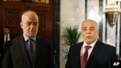 Iraq's Prime Minister Haider al-Abadi, right, stands with Iraqi Foreign Minister Ibrahim al-Jaafari at the Prime Minister's Office in Baghdad, Iraq, Jan. 21, 2015.