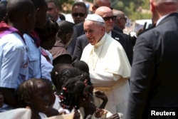 FILE - Pope Francis greets internally displaced people sheltering on the grounds of the Saint Sauveur church, during his visit in the capital Bangui, Central African Republic, Nov. 29, 2015.