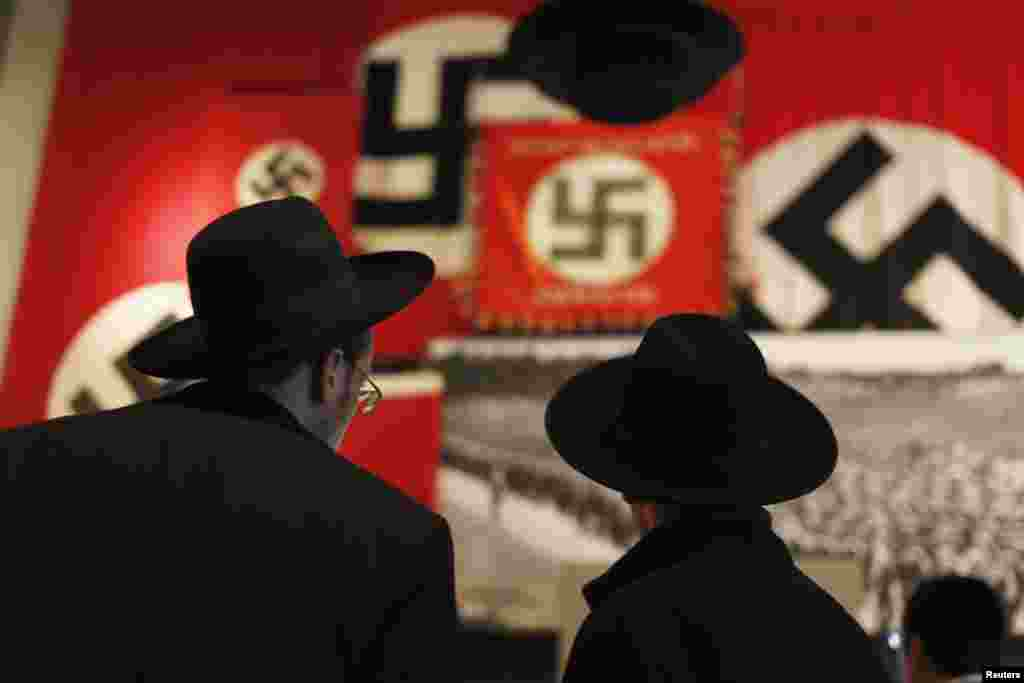 Ultra-Orthodox Jewish visitors look at a display of Nazi flags at Yad Vashem's Holocaust History Museum in Jerusalem ahead of International Holocaust Remembrance Day which will be marked on January 27.