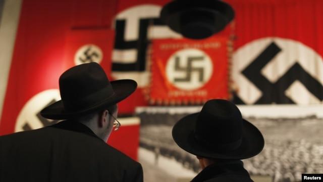Para pengunjung Yahudi Ultra-Orthodox mengamati bendera Nazi yang dipasang di museum sejarah Holokos Yad Vashem di Yerusalem, 25 Januari 2013 (REUTERS/Amir Cohen).  Majelis Umum PBB menetapkan tangal 27 Januari sebagai Hari Peringatan Holokos Internasional.