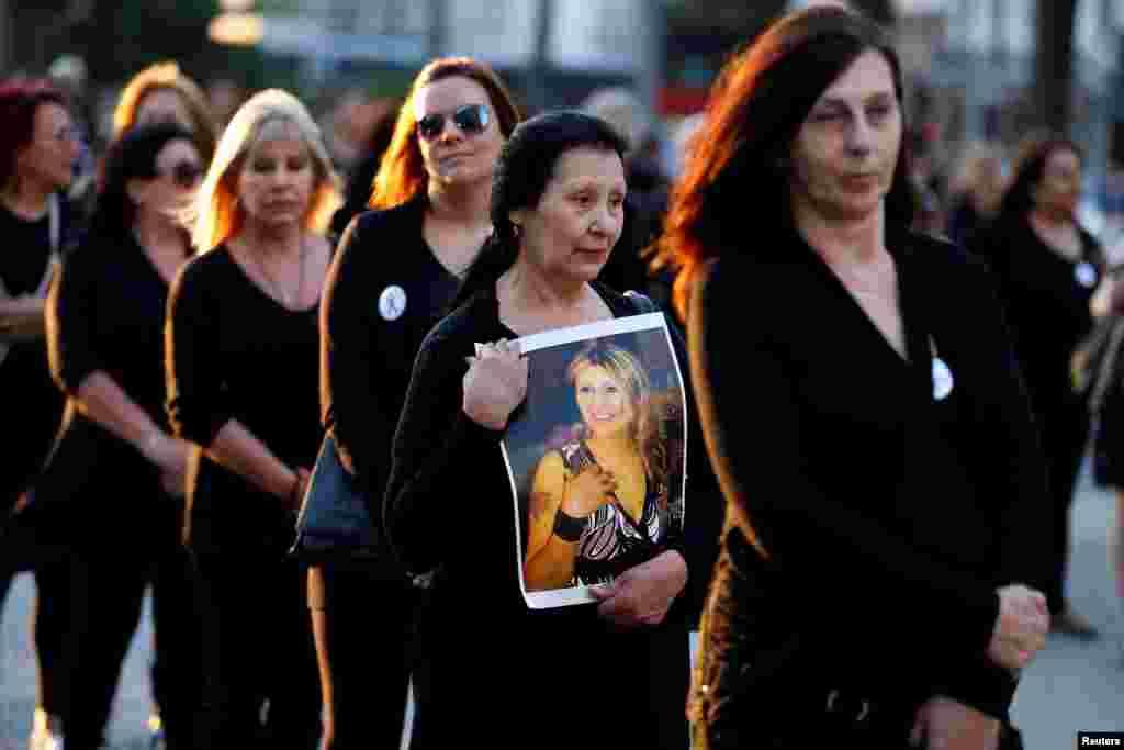 """Seorang perempuan membawa foto putrinya, yang merupakan korban kekerasan dalam rumah tangga, dalam demonstrasi yang diorganisir oleh """"Mujeres de Negro"""" (Perempuan Berbaju Hitam) untuk melawan kekerasan berbasis gender di Montevideo, Uruguay (25/11). (Reuters/Andres Stapff)"""