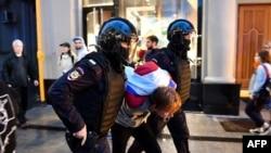 پولیس اہلکار مظاہرے میں شریک ایک شخص کو گرفتار کر کے اپنے ہمراہ لے جا رہے ہیں۔