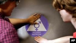 Dua murid di SMU Nathan Hale di Seattle menempelkan stiker di pintu dalam upacara peresmian kamar mandi gender netral (17/5). (AP/Elaine Thompson)