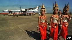 Cambodian dancers walk past a Thai airline, Bangkok Airways plane at Siem Reap's airport in northern Cambodia.
