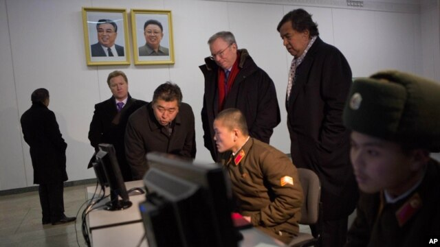 Executive Chairman of Google Eric Schmidt and former governor of New Mexico Bill Richardson look at soldiers working on computers at the Grand Peoples Study House, Pyongyang, North Korea, January 9, 2013.