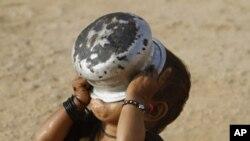 ٹھٹہ کے قریب ایک دو سالہ پاکستانی بچی ایک خالی برتن سے پانی پینے کی کوشش کررہی ہے۔