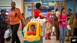 ក្មេងប្រុសម្នាក់លេងនៅក្នុងរទេះដាក់ឥវ៉ាន់ក្នុងផ្សារទំនើប ខណៈដែលអ្នកដើរទិញឥវ៉ាន់ដទៃទៀតចូលមកទិញទំនិញនៅផ្សារទំនើប Westgate Shopping Mall ក្នុងរដ្ឋធានីណៃរ៉ូប៊ី ប្រទេសកេនយ៉ា កាលពីថ្ងៃទី១៨ ខែកក្កដា ឆ្នាំ២០១៥។