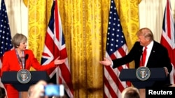 FILE - British Prime Minister Theresa May and U.S. President Donald Trump during their joint news conference at the White House in Washington, Jan. 27, 2017. Both the Trump presidential campaign and the Brexit campaign used Big Data to reach voters.