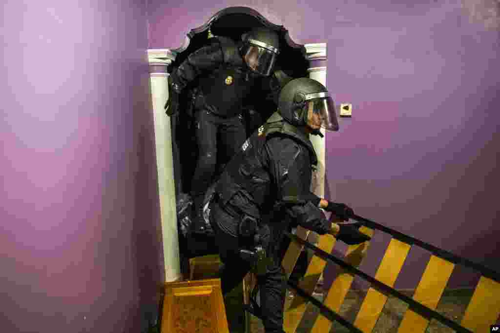 Police enter the apartment of Emilia Montoya Vazquez by forcing their way in between furniture after they broke down the main door to evict her and her family in Madrid, Spain. Montoya, who lived with her son and daughter in law, both unemployed, and three grandchildren of 7, 6, 3 years old, had accumulated a debt with the (EMV) City Hall Housing Company as she could not afford to pay the rent due to her only income - a state benefit of 460 euros ($522) a month.