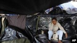 Una mujer salvadoreña espera a saber si la mayor parte de los migrantes deciden trasladarse del campamento en que se encuentran tras una invitación del gobierno municipal para ir a un nuevo refugio en Tijuana, México.