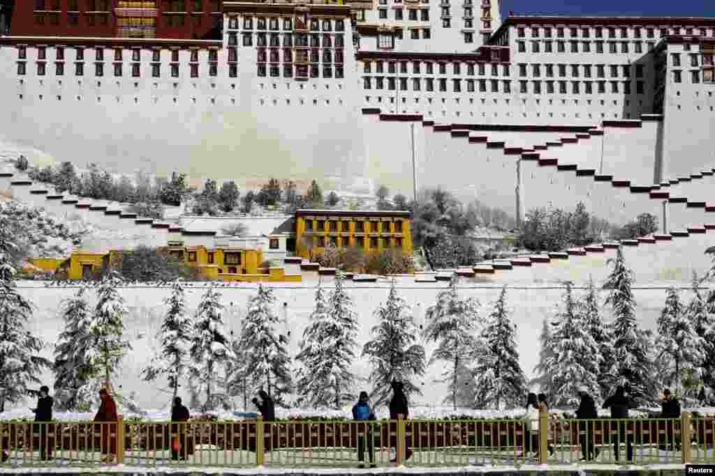 2018年12月19日,中国西藏自治区拉萨布达拉宫外,人们走过白雪覆盖的树木。被中国当局视为敏感地区的西藏自治区的官方2019年1月10日宣布,将在今年完善境外游客进藏旅游管理办法,争取将进藏审批时间缩短一半、境外游客人数增加五成。此前,美国去年12月19日通过的《西藏旅行对等法》法案旨在反击中国严格限制包括美国人在内的外国人进入西藏。法案要求中国政府必须允许美国记者、外交官和游客不受限制地前往西藏;美国国务卿必须每年向国会递交报告,指证涉及相关限制政策的中国官员,这些官员将被限制进入美国。目前中国的外交官、记者、游客等能在美国各地自由旅行,但是中国当局长期以来一直限制美国公民访问或享有进入西藏的同等权利。根据外交对等原则,国与国之间应向对方公民提供对等的权利。