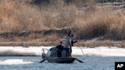 FILE - North Korean fishermen work from their boat in the Yalu River, as seen from Dandong in northeastern China's Liaoning Province, Tuesday, Feb. 9, 2016.