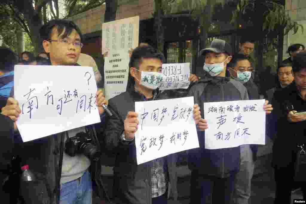 Demonstrators hold banners outside the headquarters of Southern Weekly newspaper in Guangzhou, Guangdong province, China, January 8, 2013.