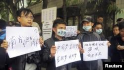 1月8日,示威者手持标语牌站在广州南方周末报社的总部的外面
