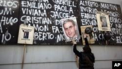 Una persona coloca un globo negro junto a los nombres de las víctimas del atentado iraní contra las instalaciones de una asociación judía en Buenos Aires, en 1994.