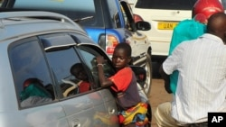 FILE - A Ugandan street child begs as traffic passes by, in Kampala, July 17, 2014.