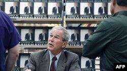 """Bivši američki predsednik Džordž Buš u razgovoru sa kupcem njegove knjige """"Odlučujući trenuci"""" u knjižari u blizini njegove kuće u Dalasu u saveznoj državi Teksas, 9. novembar 2010."""
