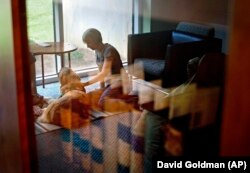 Law student Amelia Myers, 25, is reflected in a book case in the law library as she plays with Hooch, a 19-month-old golden retriever, between final exams at Emory University in Atlanta.