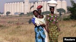 Malawian women walk past empty grain silos in the capital Lilongwe.