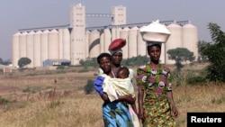 Malawian women walk past empty grain silos in the capital Lilongwe, (File photo).