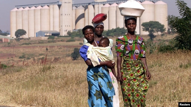 Malawian women walk past empty grain silos in the capital Lilongwe.