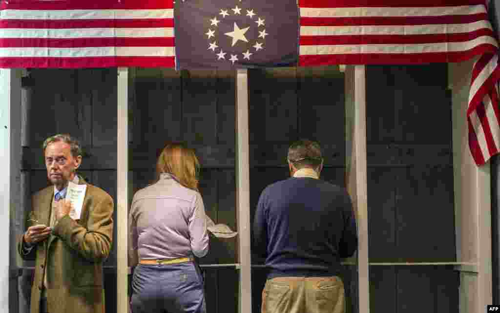 People prepare to cast their ballots inside a polling station just after midnight on November 6, 2012 in Dixville Notch, New Hampshire, the very first voting to take place in the 2012 U.S. presidential election.