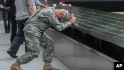 Army Sgt. Edwin Morales prays during a ceremony at the World Trade Center site in New York, Sept. 11, 2015.