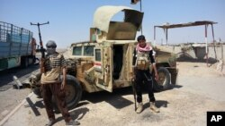 Al-Qaida inspired militants stand with a captured Iraqi army Humvee at a checkpoint outside Beiji refinery, north of Baghdad, Iraq, June 19, 2014.