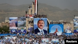 FILE - Supporters of Yemen's former President Ali Abdullah Saleh climb pillars of the Unknown Soldier Monument during a rally to mark the 35th anniversary of the establishment of the General People's Congress party, led by Saleh, Sanaa, Aug. 24, 2017.