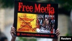 کراچی پریس کلب کے باہر ایک مظاہرے میں صحافی نے میڈیا پر پابندیاں کا پلے کارڈ اٹھا رکھا ہے ۔ فوٹو رائٹرز