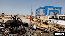 Warga memeriksa lokasi serangan bom mobil di Baghdad, Selasa (13/5).