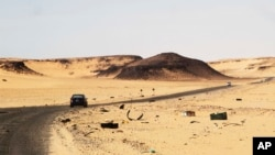 FILE - A car driving along the bandit-plagued road between Sebha and Ubari in southwestern Libya, Dec. 24, 2013.