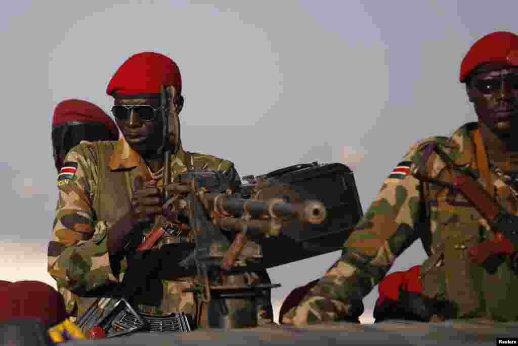 SPLA soldiers stand on a vehicle with their guns drawn, Juba, South Sudan, Dec. 20, 2013.