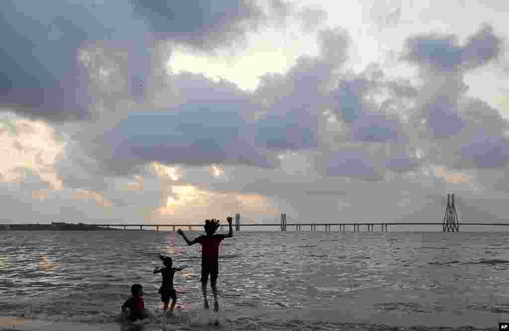 Anak-anak bermain di Laut Arab di Mumbai, India.