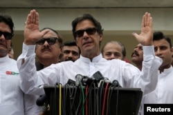 FILE - Cricket star-turned-politician Imran Khan, chairman of Pakistan Tehreek-e-Insaf (PTI), speaks to members of media after casting his vote at a polling station during the general election in Islamabad, Pakistan, July 25, 2018.