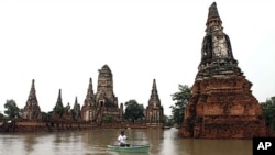 A man rows his boat past the Wat Chai Watthanaram temple which was hit by flood in Ayuttaha province, central Thailand, October 4, 2011.