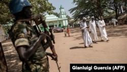 Un membre de la Minusca monte la garde alors que des musulmans quittent la Grande Mosquée dans le quartier PK5 de Bangui, le 27 novembre 2015.
