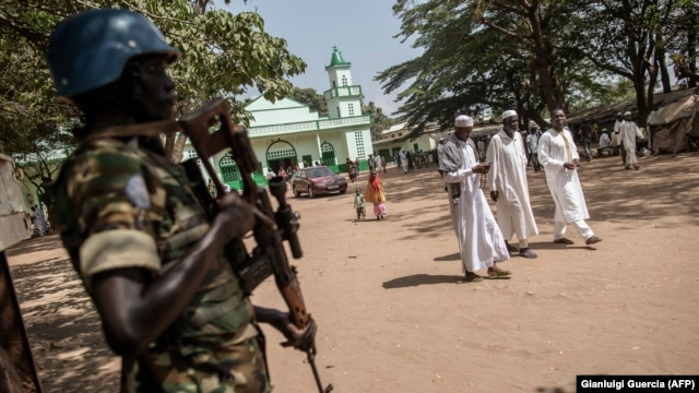 FILE - A Burundian member of the peacekeeping force from the U.N. Multidimensional Integrated Stabilization Mission in the Central African Republic (MINUSCA) stands guard as Muslims leave the Grand Mosque in the PK5 neighborhood of Bangui, Nov. 27, 2015.