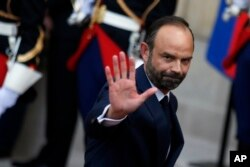 Newly appointed French Prime Minister Edouard Philippe waves after the handover ceremony with outgoing Prime Minister Bernard Cazeneuve in Paris, May, 15, 2017.
