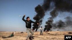 Seorang demonstran Palestina mengayunkan katapel saat terjadi bentrokan dengan pasukan Israel di Khan Yunis, kota Gaza selatan, dekat perbatasan dengan Israel (2/2).