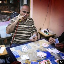 Palestinian-American Ibrahim Mussa plays cards in a Ramallah cafe