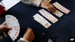 In this Tuesday, Sept. 22, 2015 file photo, competitors play bridge at the Acol Bridge Club in West Hampstead, London. A doping ban handed down to the top-ranked player in bridge has provoked a backlash in the card game. (AP Photo/Tim Ireland, File)