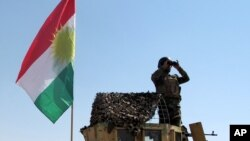 FILE - A member of the Kurdish security forces scans the horizon in Kirkuk, Iraq, from atop a military vehicle flying a flag of the Kurdistan Regional Government, June 14, 2014.