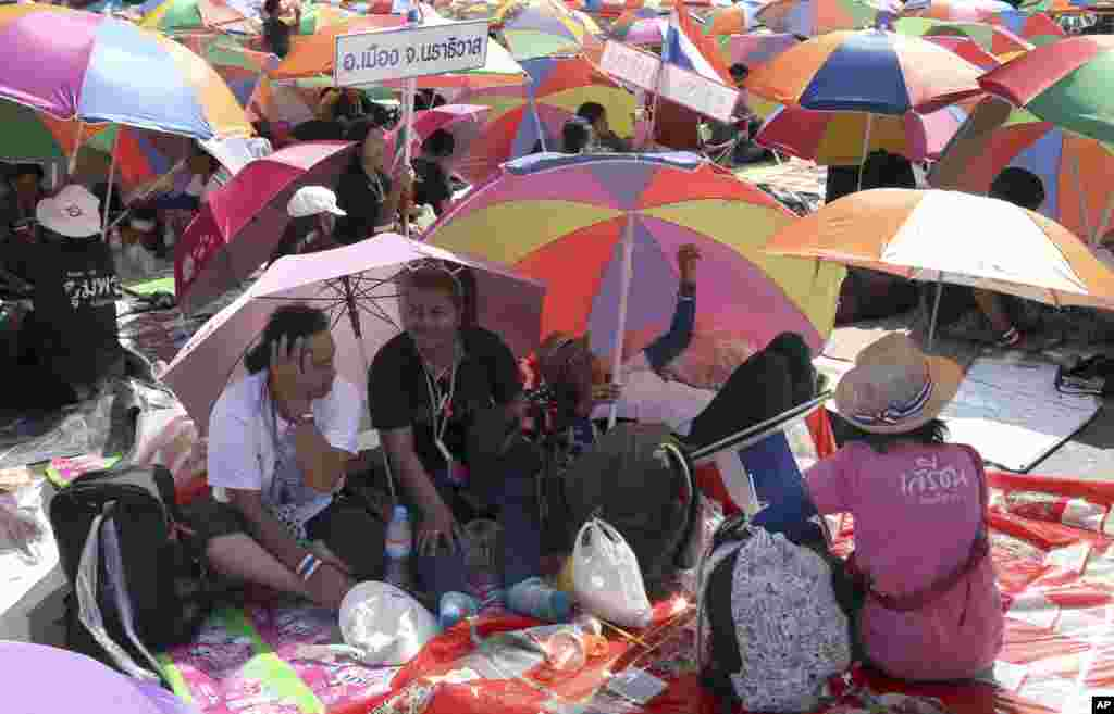 Anti-government protesters sit under beach umbrellas during a rally at the Democracy Monument, Bangkok, Thailand, Jan. 12, 2014.