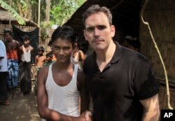 Aktor Hollywood Matt Dillon, kanan, berjabat tangan dengan Noor Alam, 17 tahun, yang selamat dari upaya penyelundupan manusia, di desa Thetkabyin, sebelah utara Sittwe, Rakhine, Myanmar